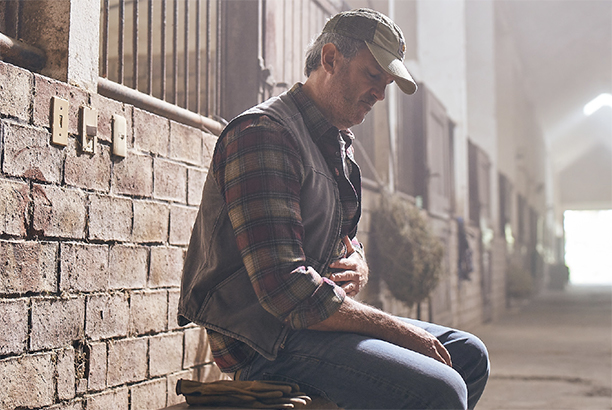 Man in a barn wearing a plaid shirt is holding his stomach due to CIC (Chronic Idiopathic Constipation) symptoms.